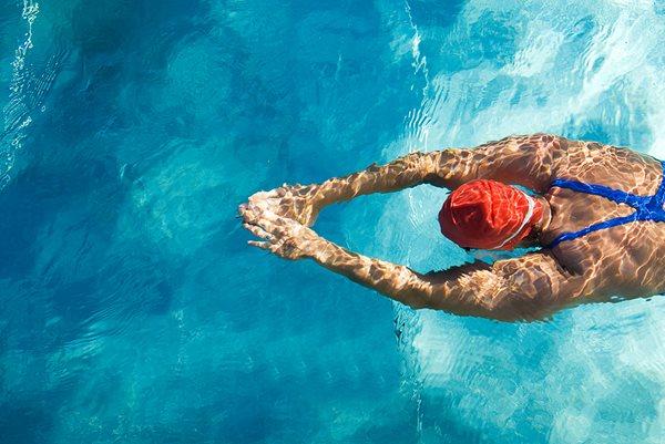 Mann beim Schwimmen mit roter Badekappe