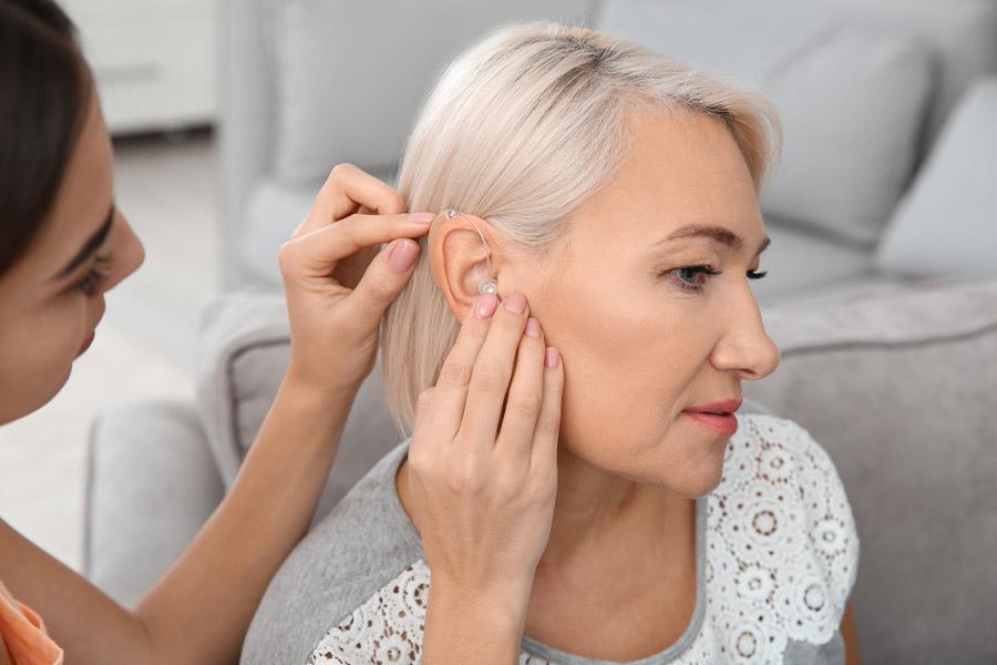 Frau bringt Hörgerät an