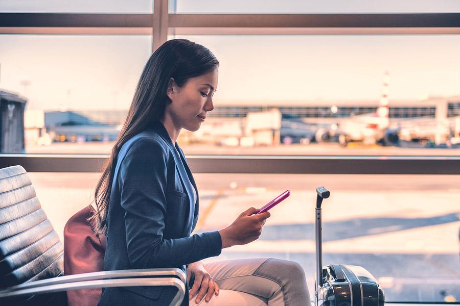 Frau mit Handy am Flughafen